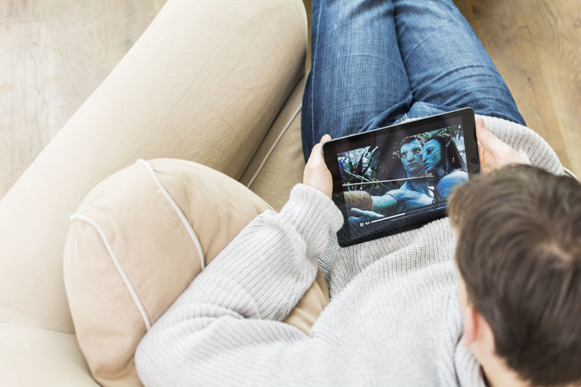 Un hombre ve una película en la tablet a través de un servicio de streaming como Netflix