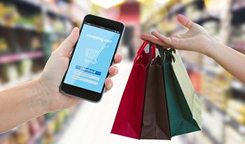 Aplicación de comercio electrónico en el móvil y bolsas con compras