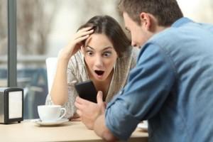 Chica mirando sorprendida un móvil que sostiene un chico