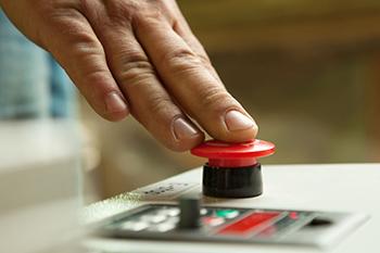 Un hombre pulsa un botón rojo de alerta