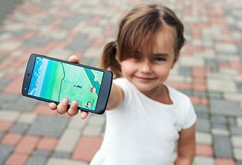 Niña muestra teléfono móvil en el juego Pokémon Go
