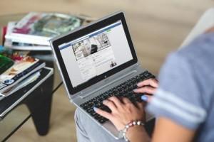 mujer consultando facebook en un portatil