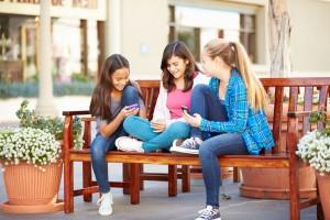Grupo de amigas que utilizan smartphones juntas