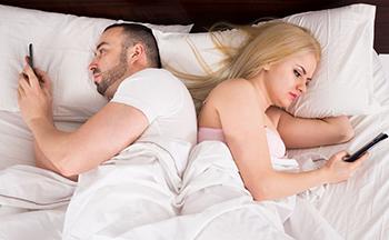 Pareja consultando sus teléfonos móviles en la cama