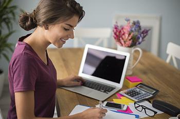 Mujer tomando notas con sus dispositivos tecnológicos