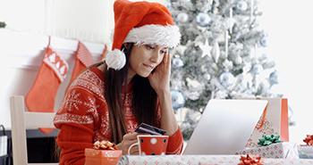 Mujer ataviada con ropa navideña realiza sus compras de Navidad por Internet