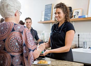 Mujer efectúa un pago con el móvil en una cafetería