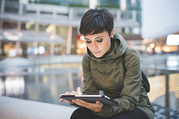 Mujer consulta su tablet en un espacio abierto
